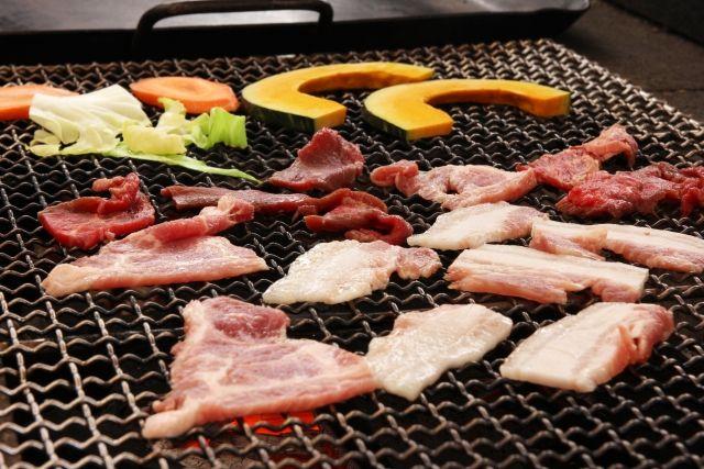バーベキューをしていて、お肉や野菜を焼いている。