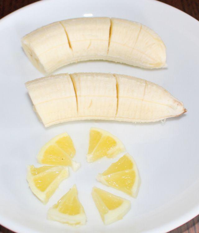 半分にしたバナナに切り込みを入れ、輪切りのレモンの皮をむき、6枚のいちょう切りにしている。